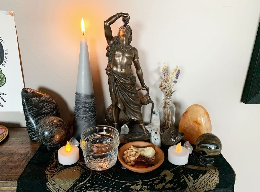 A shrine to Dionysos with offerings, candles, and crystals.